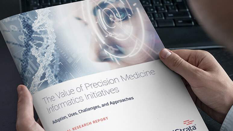 Image of business person holding a copy of the white paper, The Value of Precision Medicine Informatics Initiatives.